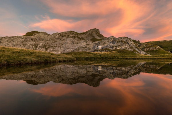 Red sky above mountain hut and lake