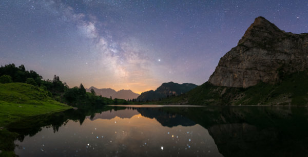 Milky way panorama reflecting in alpine lake