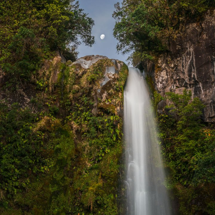 Full Moon Rising Above Waterfall in Forest
